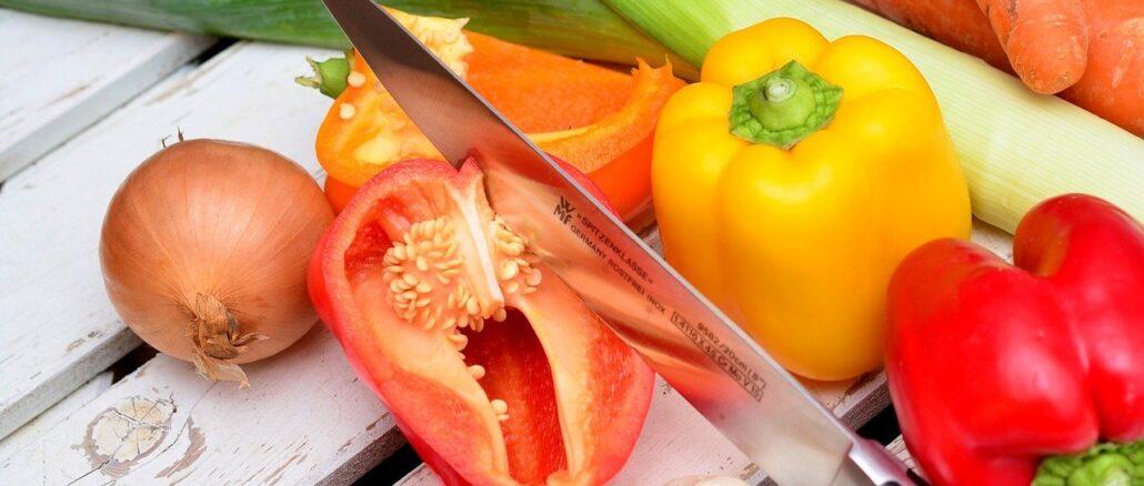 Um pimentão cortado, com uma faca cravada, ao lado mais pimentões, cenoura, alho poró, cebola, e alhos